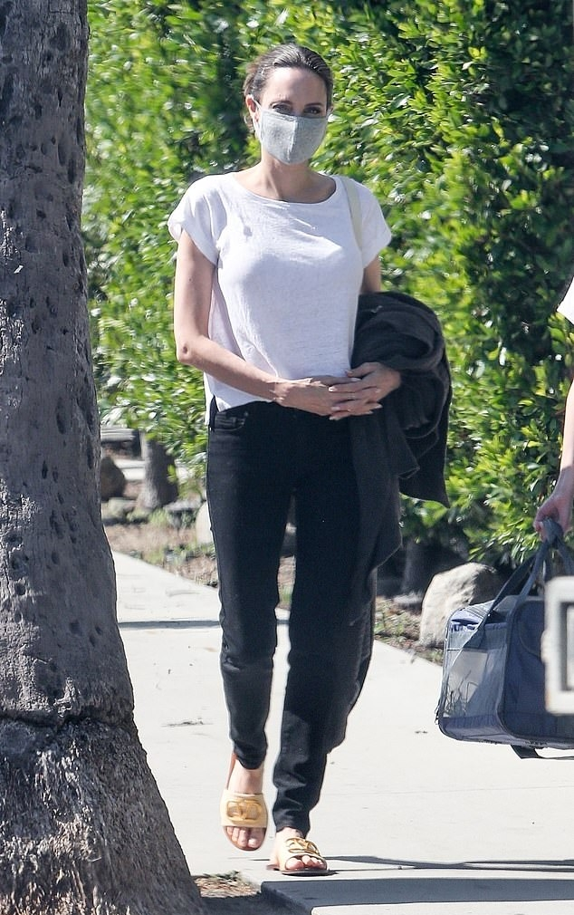 Angelina Jolie wearing brand logo cream leather open toe slide on sandal by Valentino with flat heel