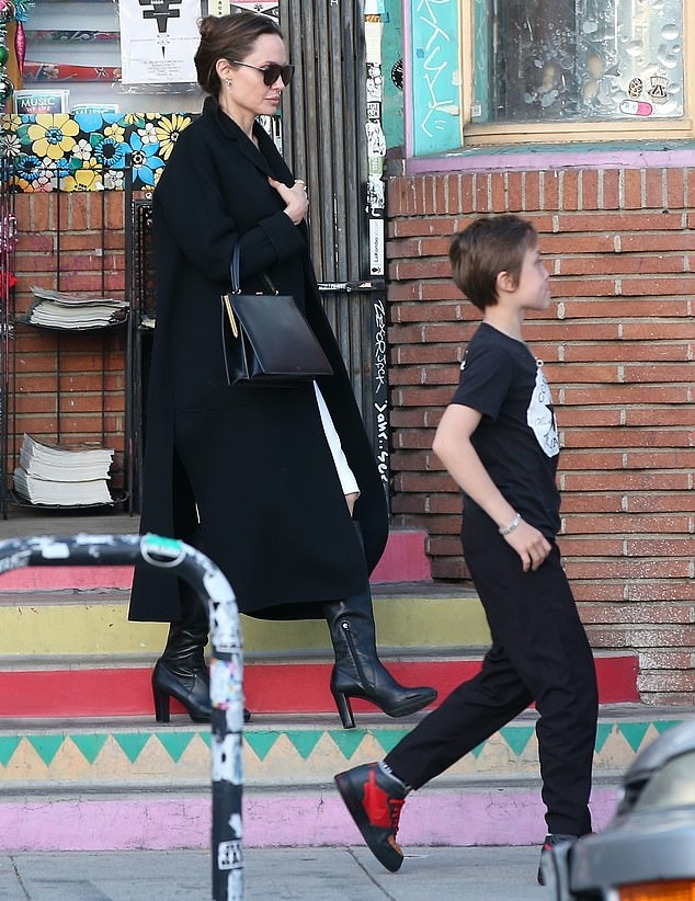 Angelina Jolie wearing pointy black leather knee high boots with high block heel