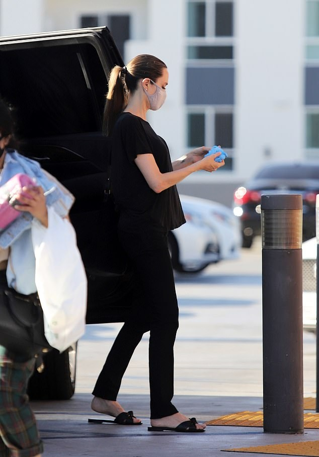 Angelina Jolie, black tee, black flats, black trousers, hip length, short sleeves, round neck, casual, basic. Angelina Jolie rocking a Black basic t shirt with short sleeves and a round neck