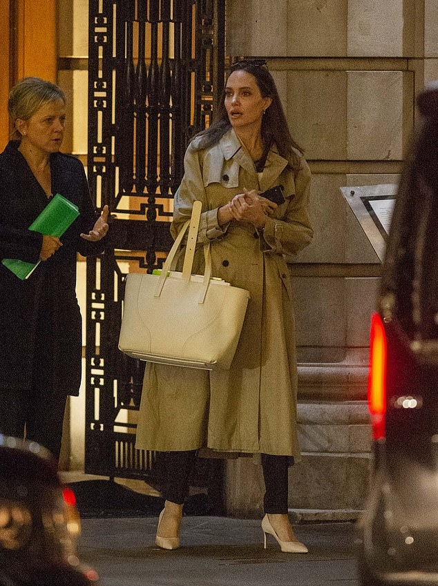 Angelina Jolie, white pumps, cream trench coat, white purse, high heel, narrow, pointy, black pants, pointy heel. Angelina Jolie rocking pointy white pumps with high heel