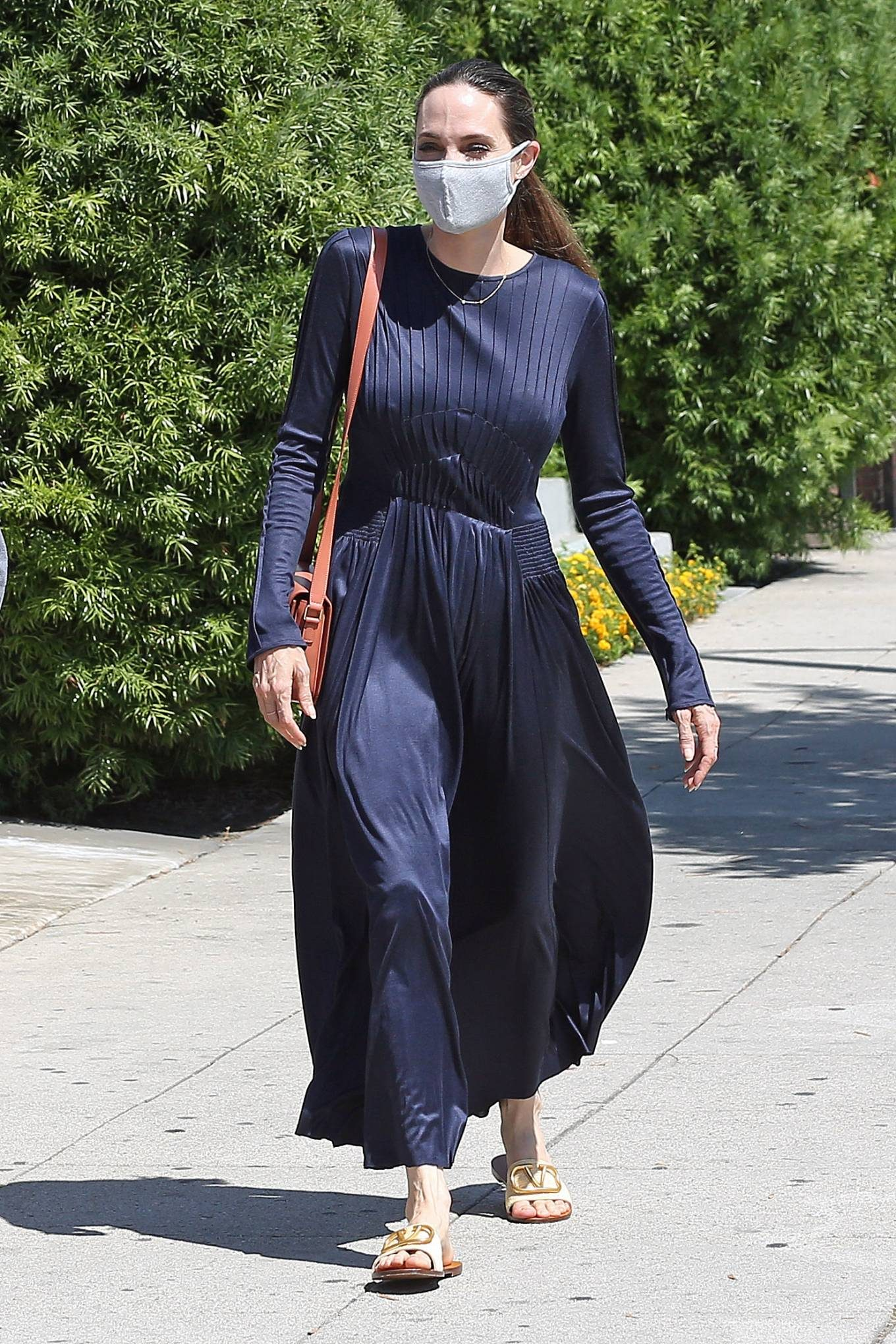 Angelina Jolie, leather, Valentino flats, cream flats, navy blue dress, tan purse, open toe, brand logo, Valentino slide on sandal, cream slide on sandal, flat heel. Angelina Jolie rocking brand logo cream leather open toe slide on sandal by Valentino with flat heel
