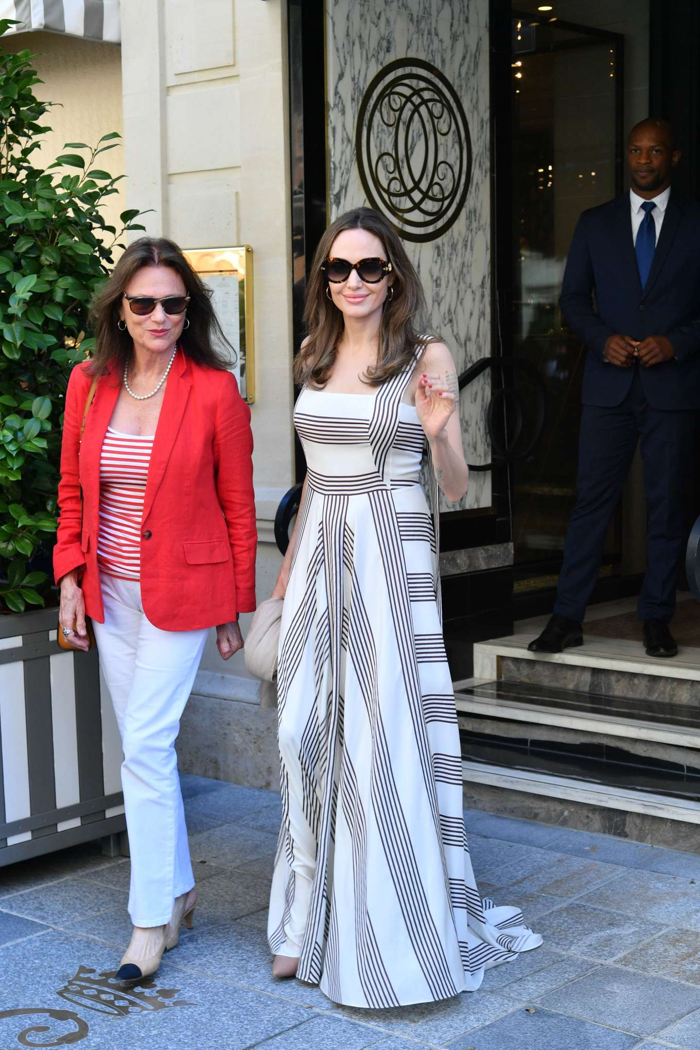 Angelina Jolie, white and black dress, black Louis Vuitton sunglasses, flared hem, straps, square neck, flowing, striped, floor scraping, a line dress, paneled, gatheres. Angelina Jolie rocking a Striped Loro Piana white maxi dress with shoulder straps actually extend down the back into ribbons, a square neck, straps and flared hem