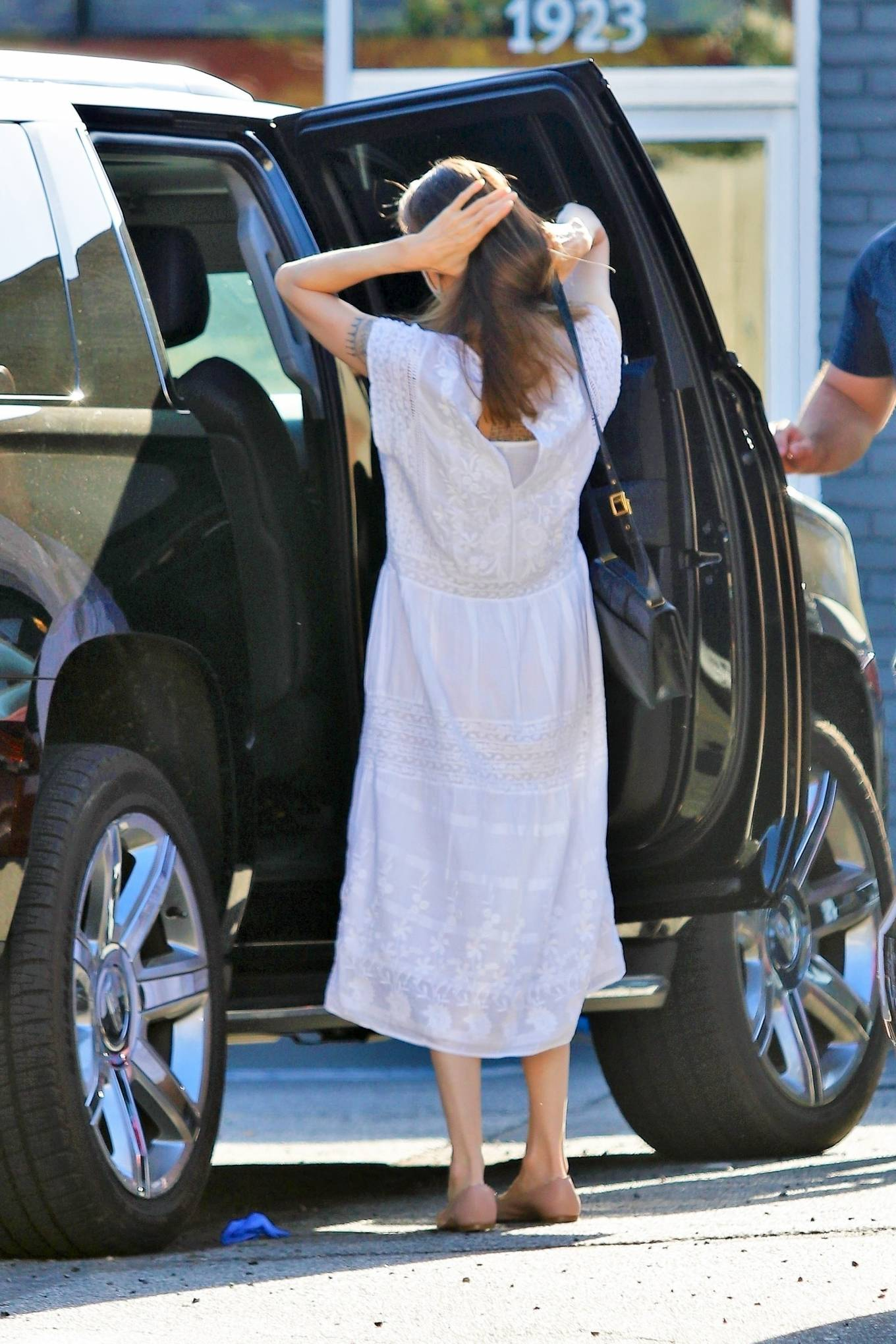 Angelina Jolie, Nude mules, leather, white dress, black purse, flat heel, round. Angelina Jolie donning round Nude leather mules with flat heel