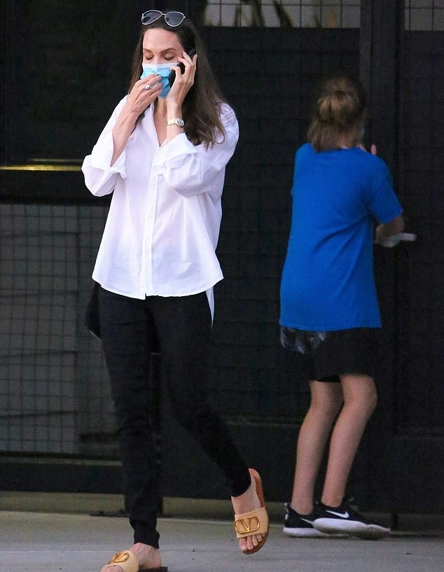 Angelina Jolie, cream flats, leather, Valentino flats, black purse, white shirt, brand logo, open toe, cream slide on sandal, Valentino slide on sandal, black trousers, flat heel. Angelina Jolie donning brand logo cream leather open toe slide on sandal by Valentino with flat heel