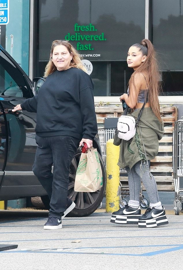 Ariana Grande rocking a skimpy grey crop top with a scoop neck and spaghetti straps
