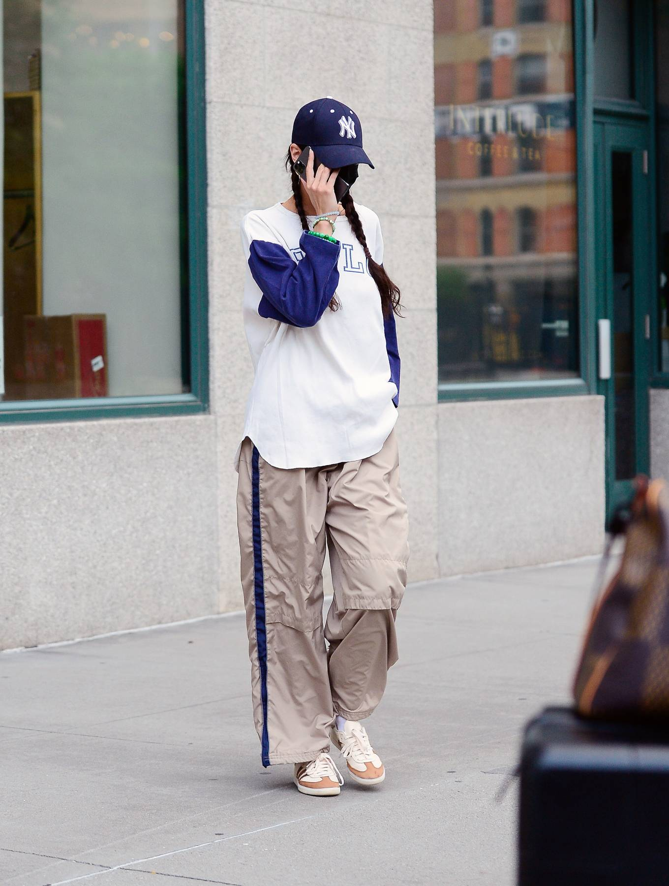 Bella Hadid, Adidas sneakers, white sneakers, oversized white graphic tee, round, lace-up, nude trousers. Bella Hadid wearing round white Adidas lace-up sneakers