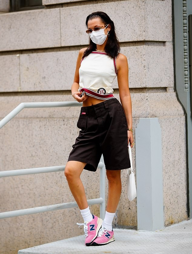 Bella Hadid donning round light pink lace-up sneakers by New Balance with flat heel