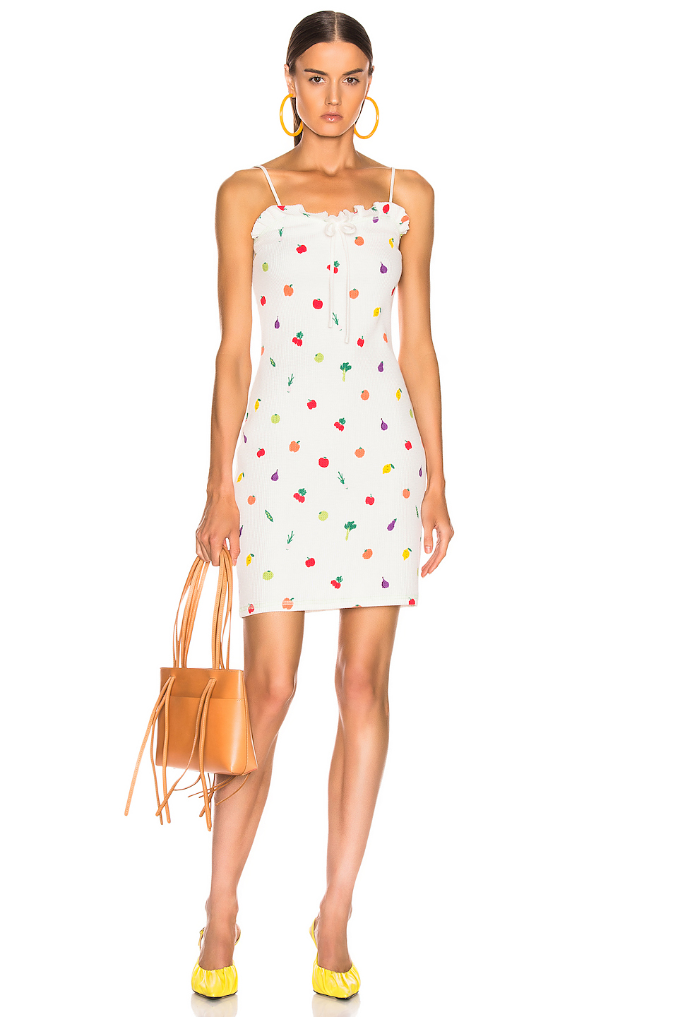 Bella Hadid wearing a Figure hugging ivory Staud salad printed mini dress with a knit fabric and thin shoulder strap
