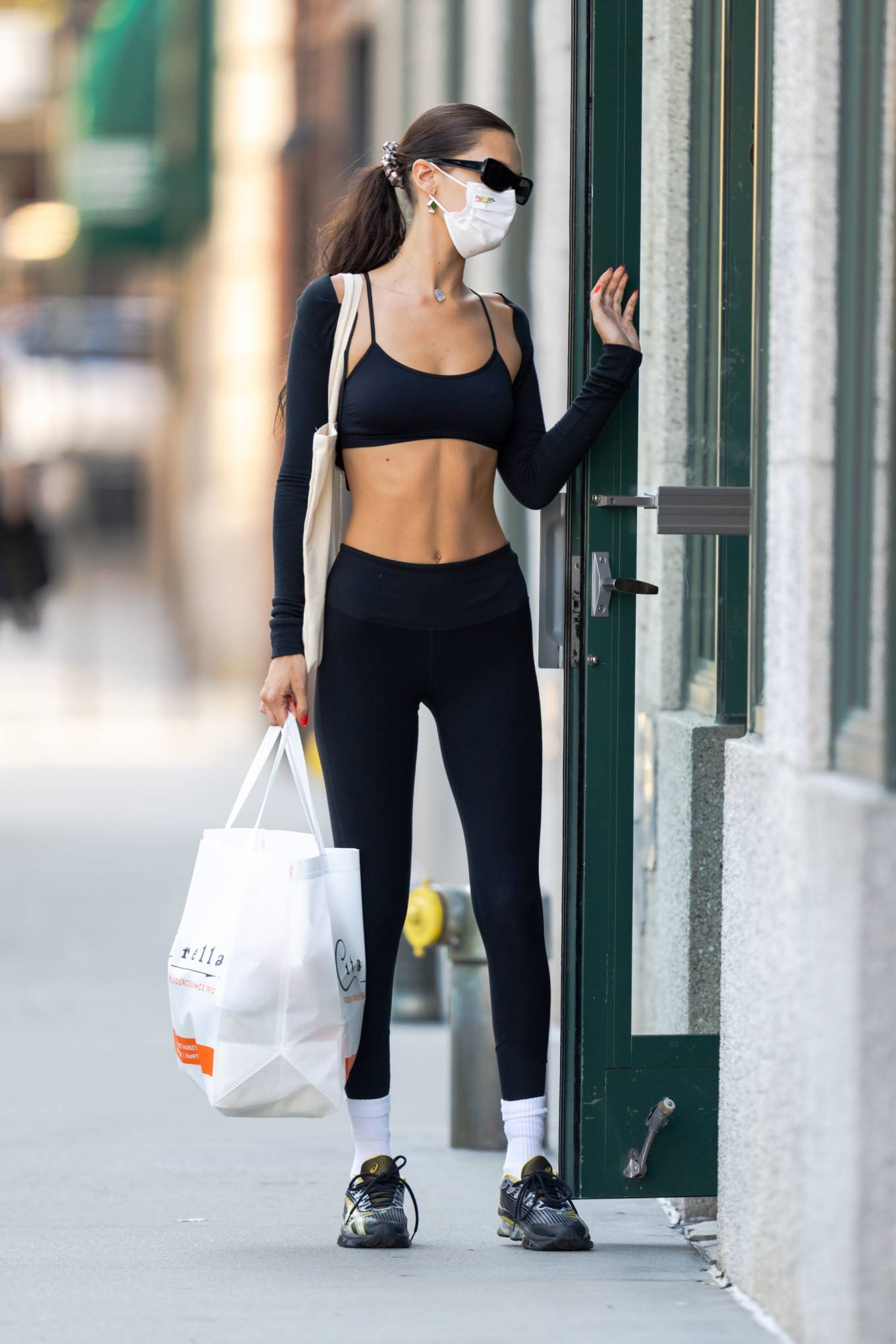 Bella Hadid wearing round black lace-up sneakers