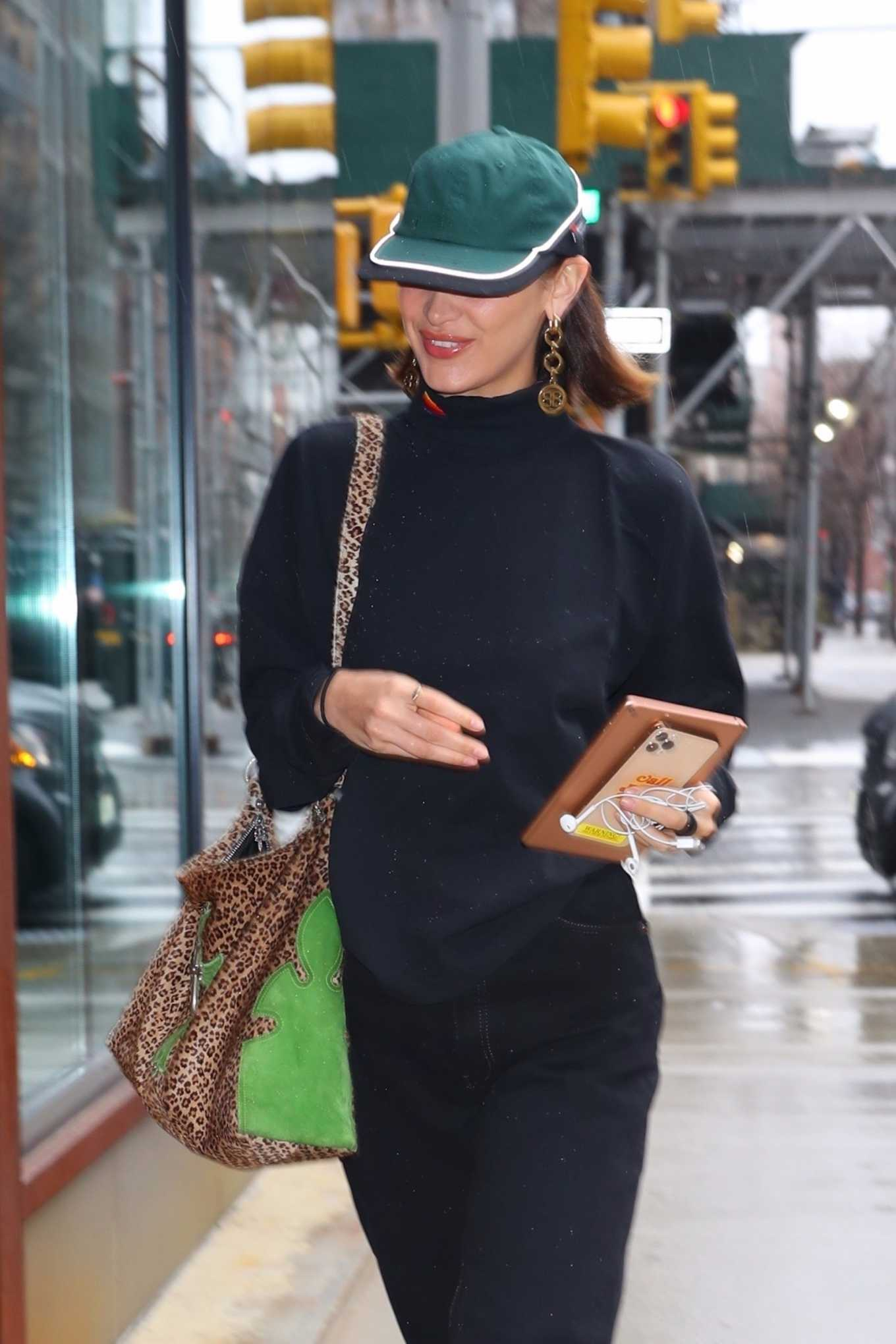 Bella Hadid, black sneakers, green purse, black sweater, round, lace-up, canvas, grey sneakers, black jeans. Bella Hadid donning round black grey lace-up sneakers