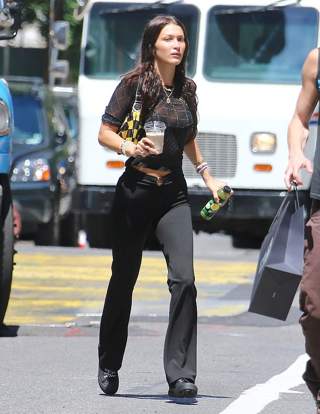 Bella Hadid wearing round black lace-up sneakers with flat heel