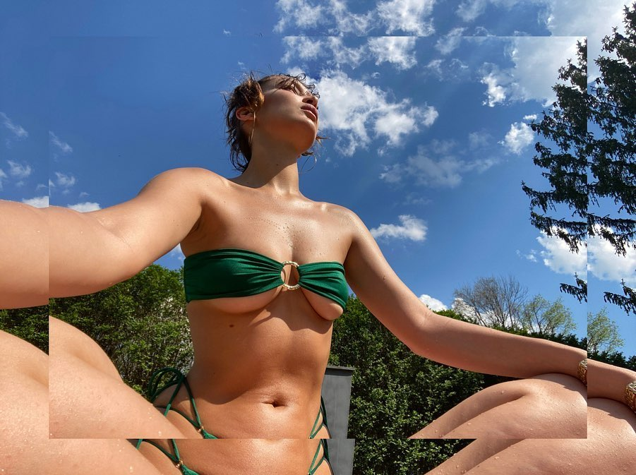 Bella Hadid donning a Skimpy dark green bikini top with ruched and a very low cut sweetheart neckline