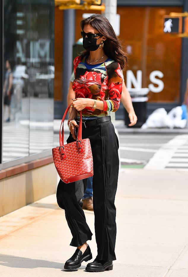 Bella Hadid wearing relaxed fit black mid rise trousers with side pockets