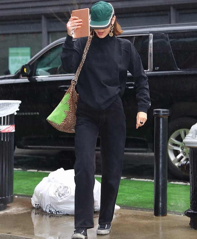 Bella Hadid, black sneakers, black sweater, green purse, round, lace-up, canvas, grey sneakers, black jeans. Bella Hadid donning round black grey lace-up sneakers