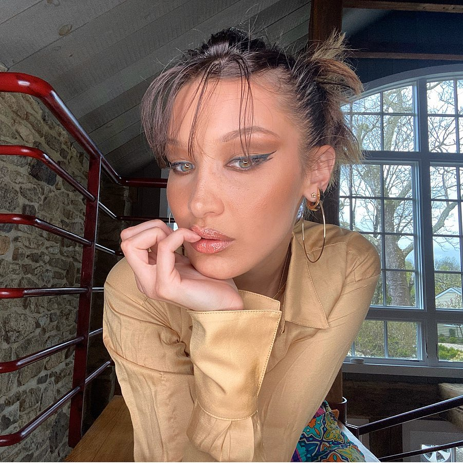 Bella Hadid wearing a Sexy nude satin shirt with a satin fabric, full sleeves, mandarin collar, button front and curved hem