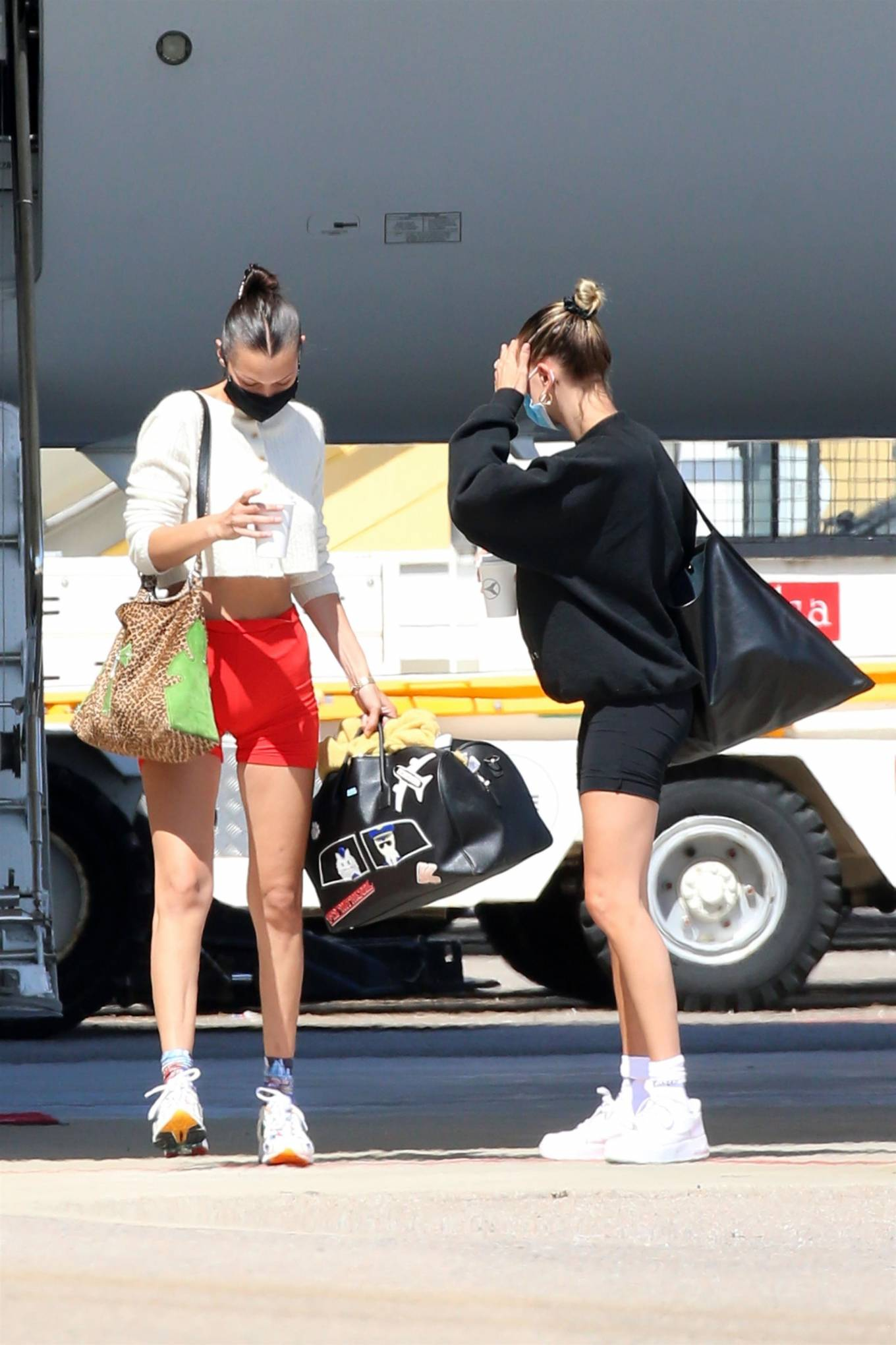Bella Hadid, off white Musier Paris cardigan, white New Balance sneakers, little, high waist, skinny, showcase, black Karl Lagerfeld travel bag, sportswear inspired, flat stomach, long legs