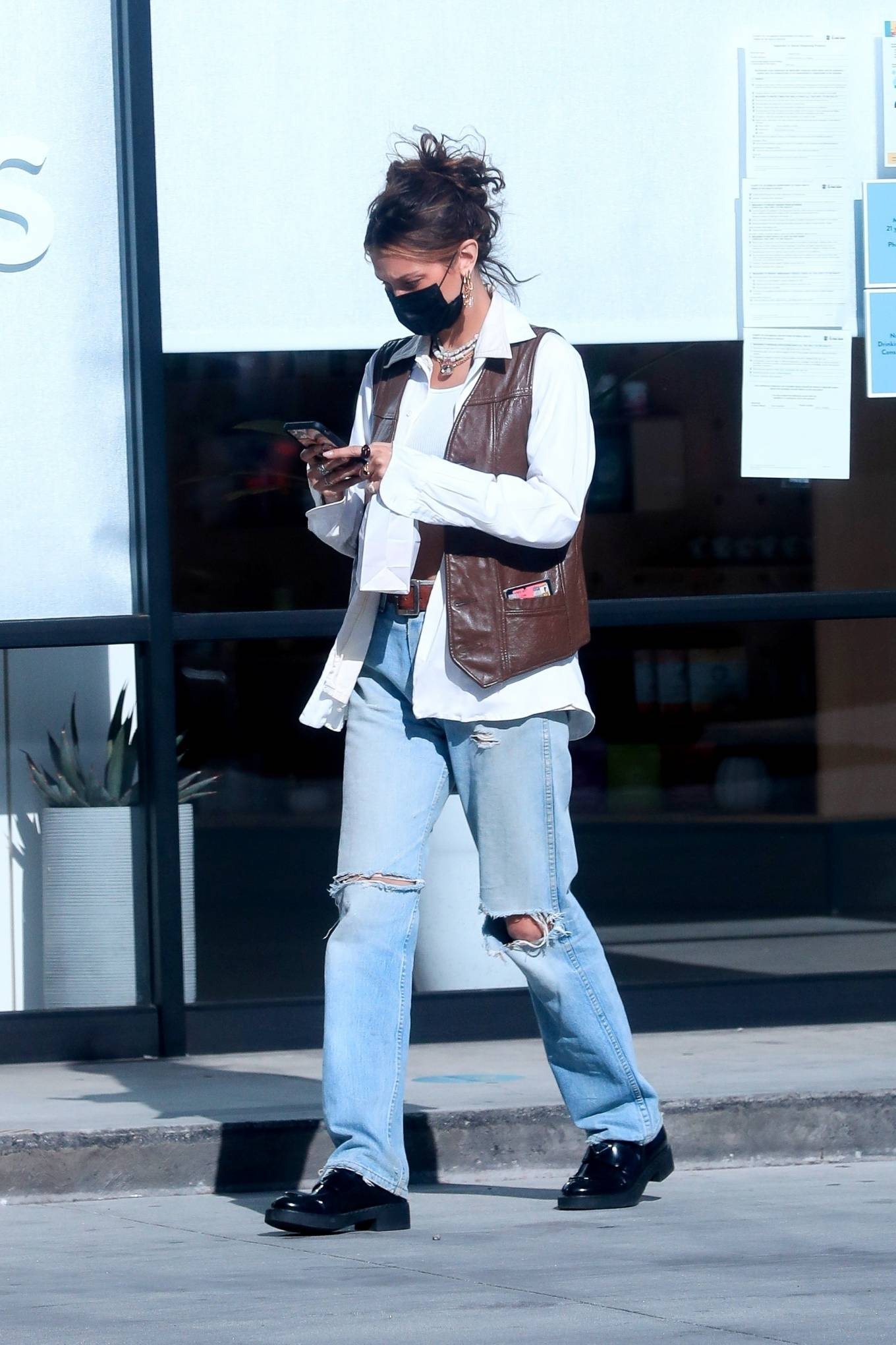 Bella Hadid rocking a brown open front leather vest with welted pockets