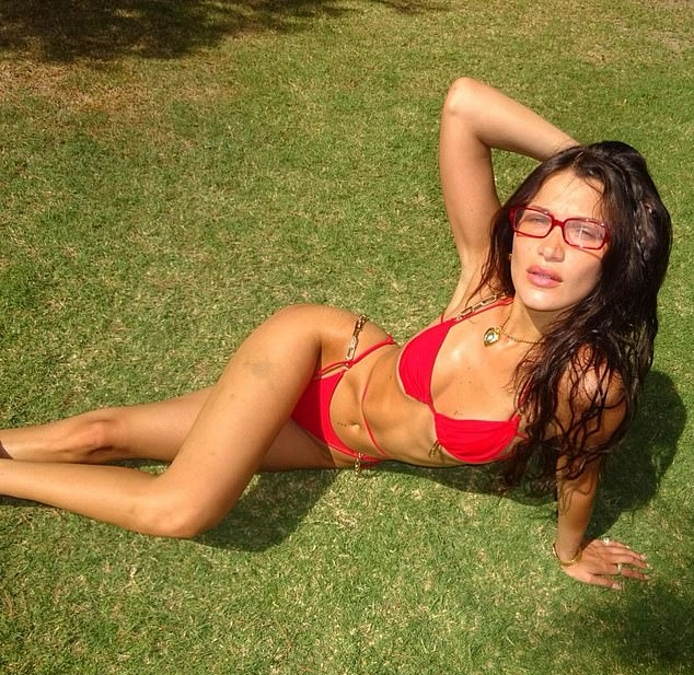 Bella Hadid, red bikini top, figure hugging red bikini bottom, red treasure glasses, chest length, straps, plunging, skimpy, flat stomach, fitted, abs, bikini body. Bella Hadid rocking a plunging red bikini top with straps