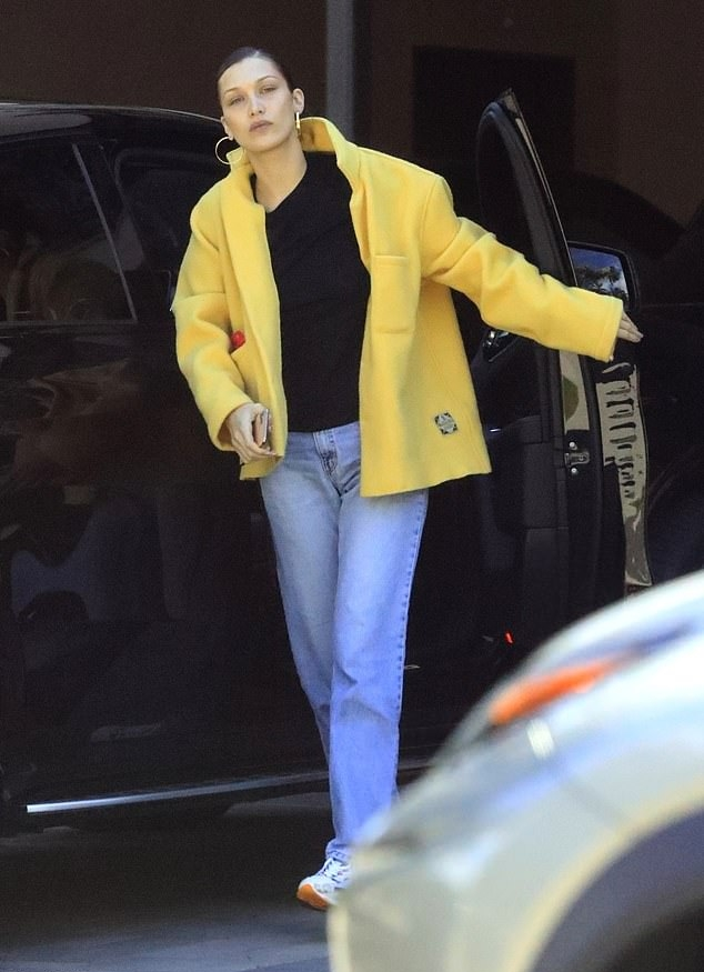 Bella Hadid donning chunky white blue lace-up sneakers by New Balance