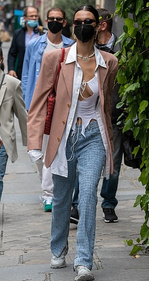 Bella Hadid donning a fitted light pink blazer with full sleeves, lapel collar and flap pockets