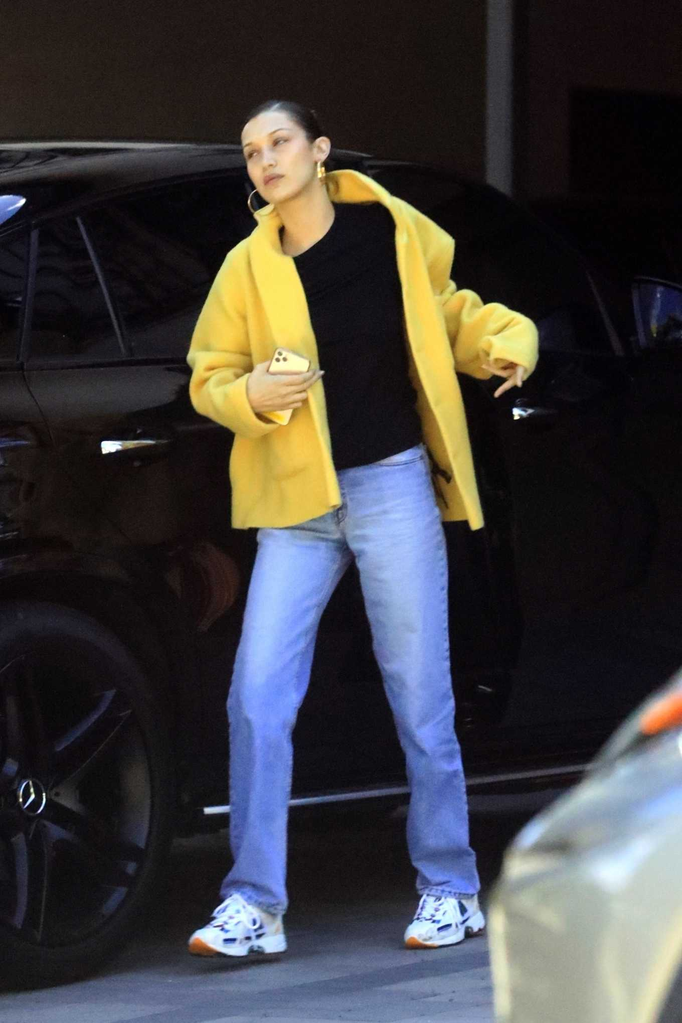 Bella Hadid, white sneakers, leather, yellow jacket, chunky, blue sneakers, black tee, lace-up, light blue jeans. Bella Hadid donning chunky white blue lace-up sneakers by New Balance