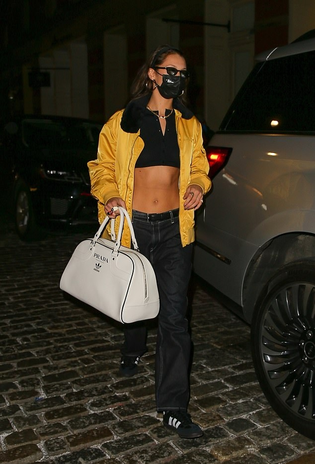 Bella Hadid wearing round black Adidas lace-up sneakers with flat heel