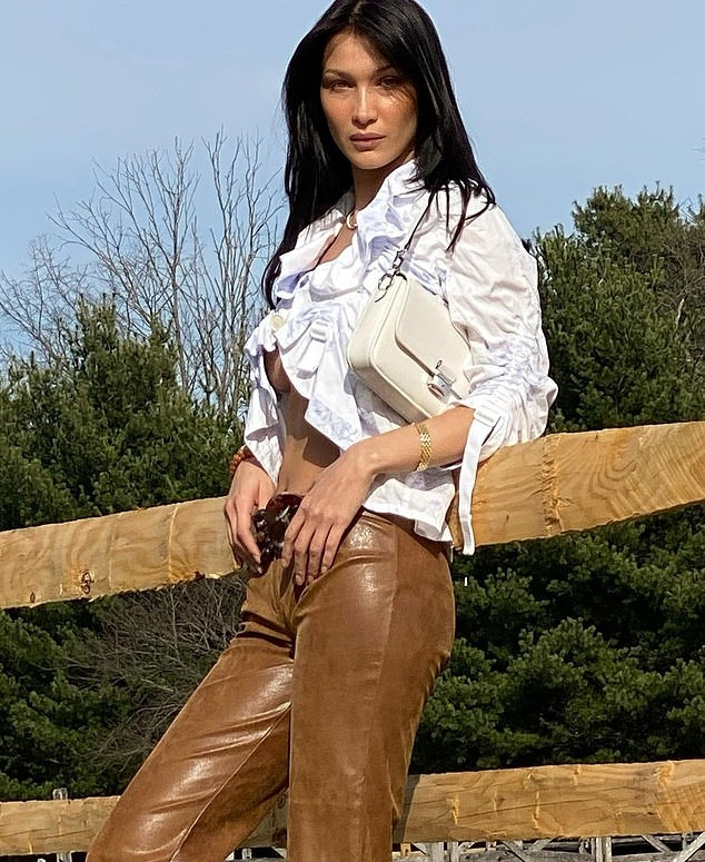 Bella Hadid wearing straight fit shiny brown flared hem trousers