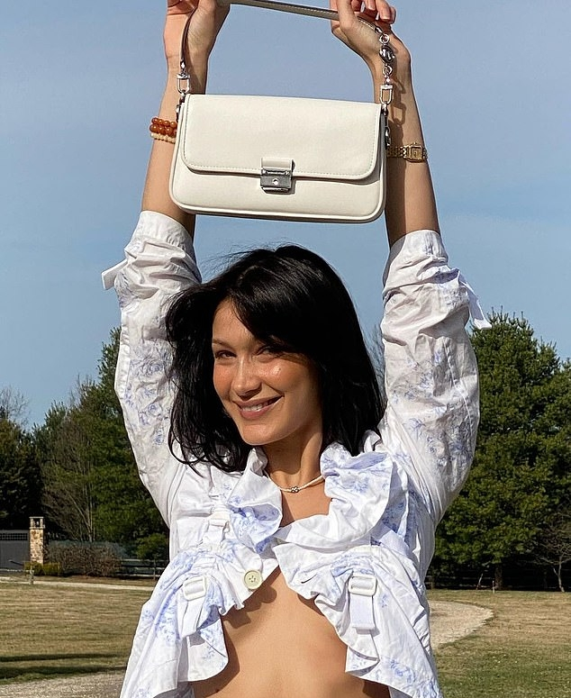 Bella Hadid, white top, white Michael Kors shoulder bag, brown trousers, 34 sleeves, sexy, flawless cleavage, ruffled, racy, open front, underboobs, ruched, on the back, flat stomach. Bella Hadid donning a sexy white top with 3/4 sleeves and ruched