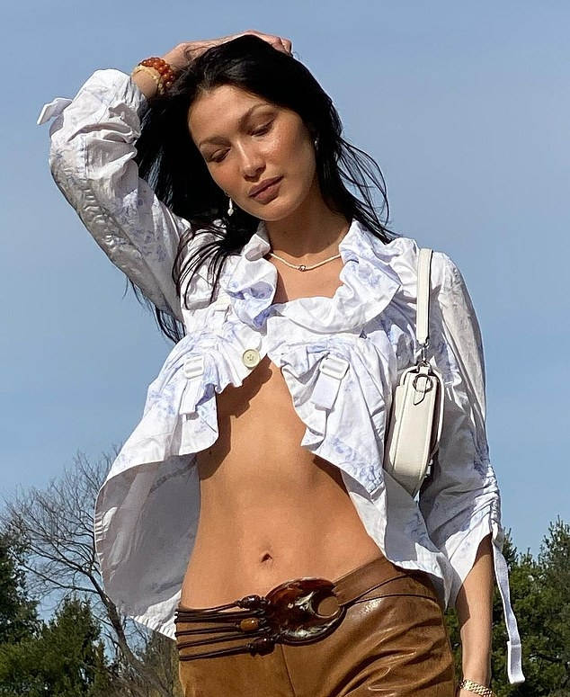 Bella Hadid, white top, brown trousers, white Michael Kors shoulder bag, racy, 34 sleeves, sexy, flawless cleavage, ruffled, on the back, open front, underboobs, ruched, flat stomach. Bella Hadid donning a sexy white top with 3/4 sleeves and ruched