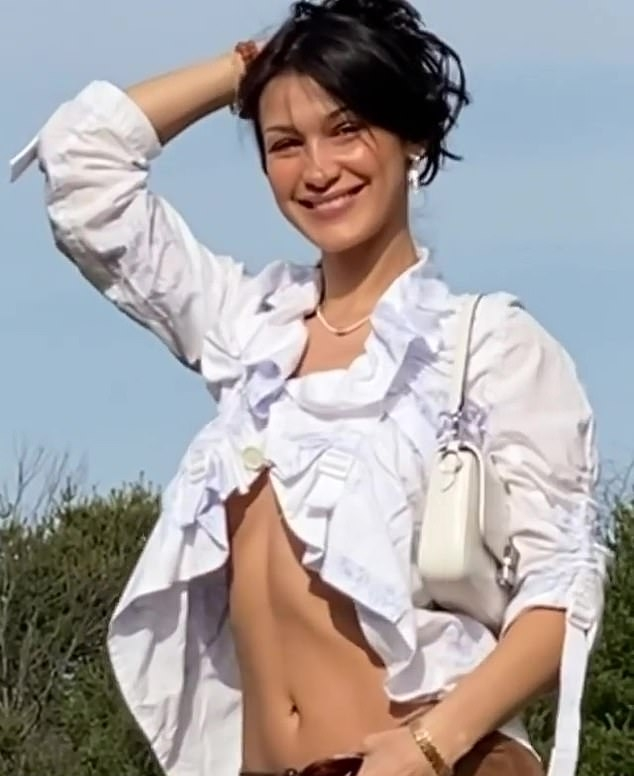 Bella Hadid, white top, white Michael Kors shoulder bag, brown trousers, ruffled, racy, 34 sleeves, sexy, flawless cleavage, ruched, on the back, open front, underboobs, flat stomach. Bella Hadid donning a sexy white top with 3/4 sleeves and ruched