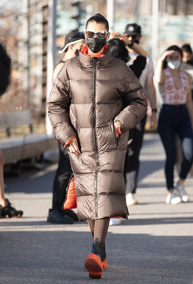 Bella Hadid rocking a oversized brown printed motifs puffer jacket with full sleeves, side pockets and a funnel neck