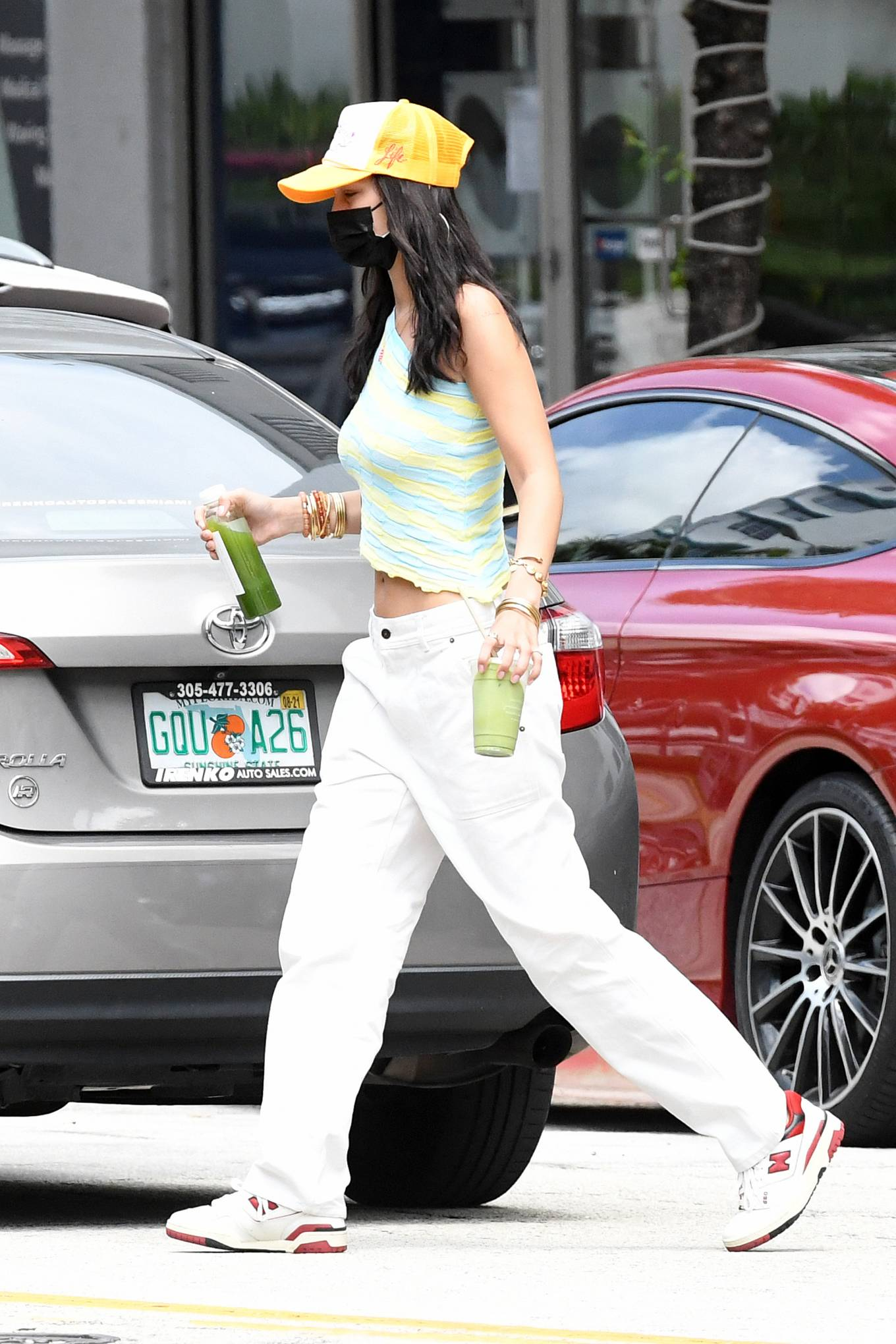 Bella Hadid wearing brand logo white red lace-up sneakers by New Balance with flat heel