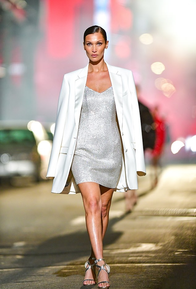 Bella Hadid donning strappy silver ankle sandals with high heel and ankle strap