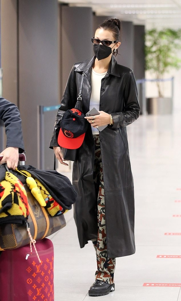 Bella Hadid donning a shiny black open front leather long jacket with full sleeves, shirt collar and button front