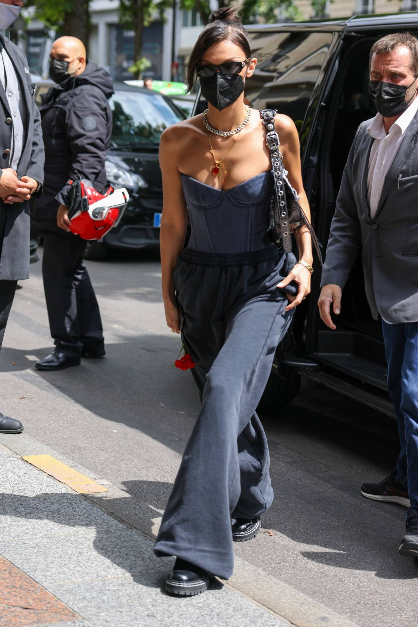 Bella Hadid wearing relaxed fit black high waist trousers with side pockets