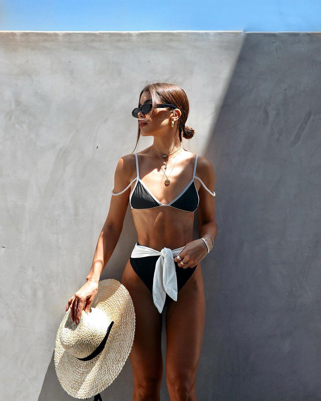 Camila Coelho donning a Plunging black Camila Coelho bikini top with strappy and spaghetti straps