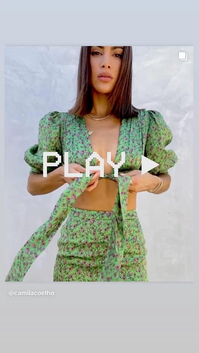 Camila Coelho rocking a shiny green matching satin mini skirt