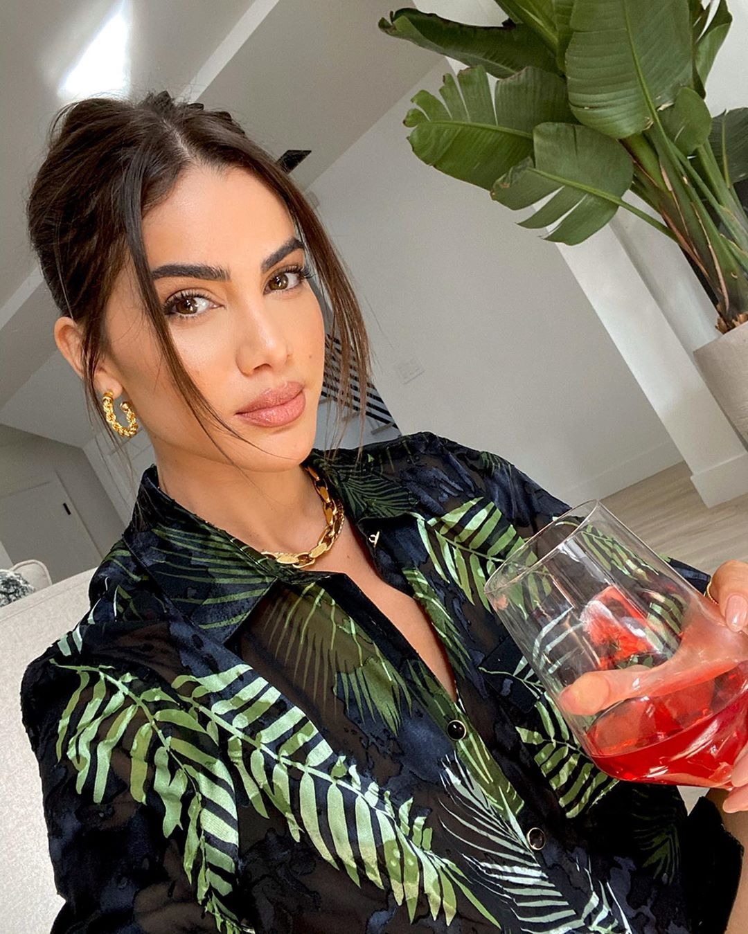 Camila Coelho donning a Oversized shiny black Camila Coelho floral shirt with a satin material, elbow length sleeves, shirt collar, floral print and curved hem
