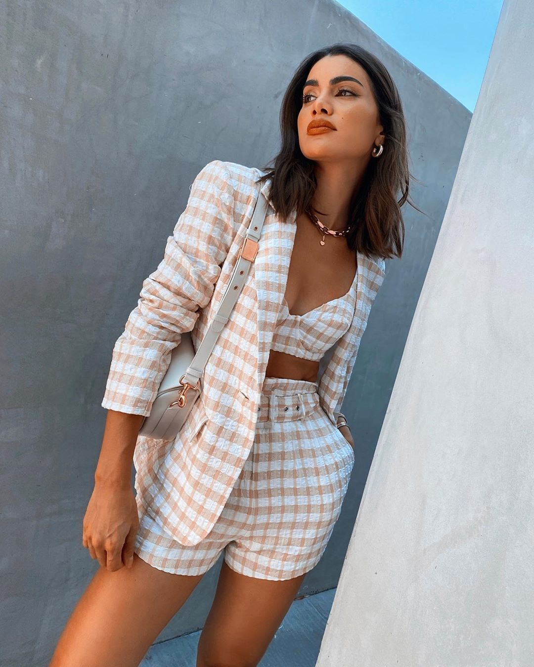 Camila Coelho donning a White beige checks printed Camila Coelho crop top with a very low cut sweetheart neckline and spaghetti straps