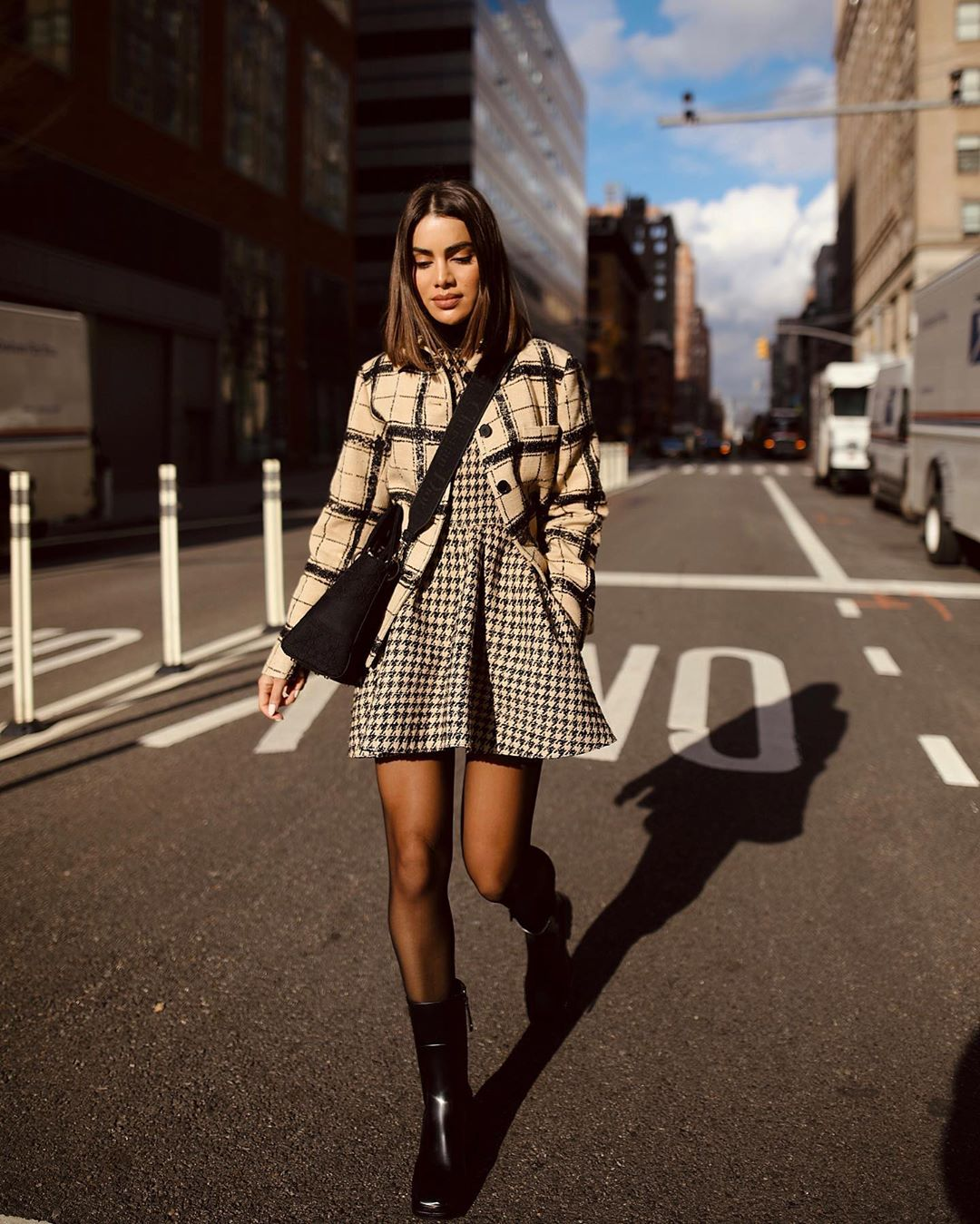 Camila Coelho wearing a cream button front jacket with extra long sleeves and shirt collar