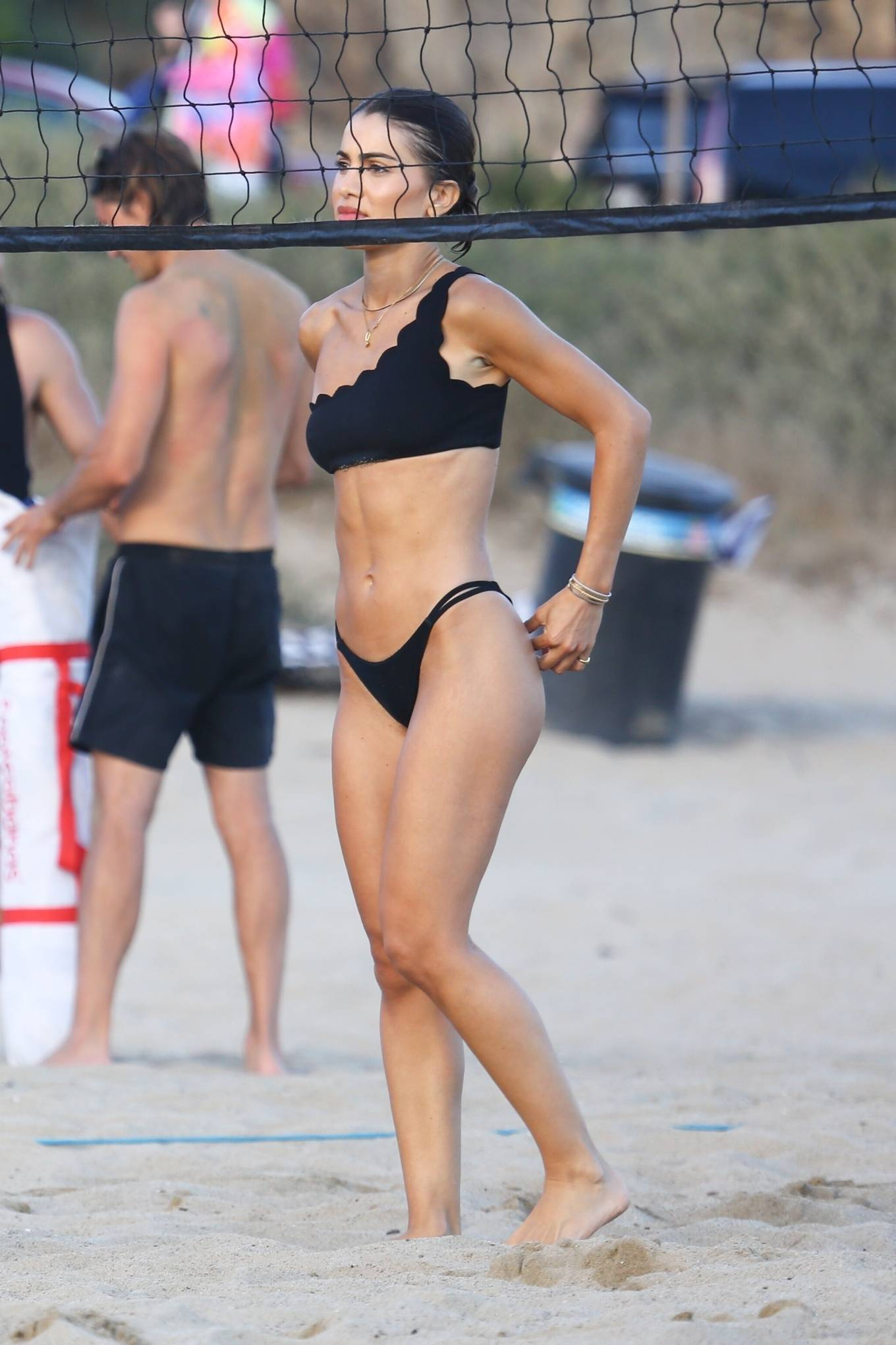 Camila Coelho donning a Skimpy black bikini top with one shoulder, a asymetrical neckline and scallop hem