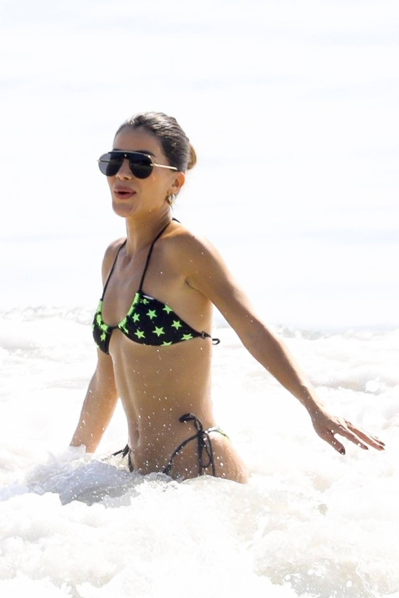 Camila Coelho, black bikini top, black sunglasses, display, neon green star printed, sexy, spaghetti straps, very low neck, skimpy. Camila Coelho rocking a plunging black bikini top with spaghetti straps