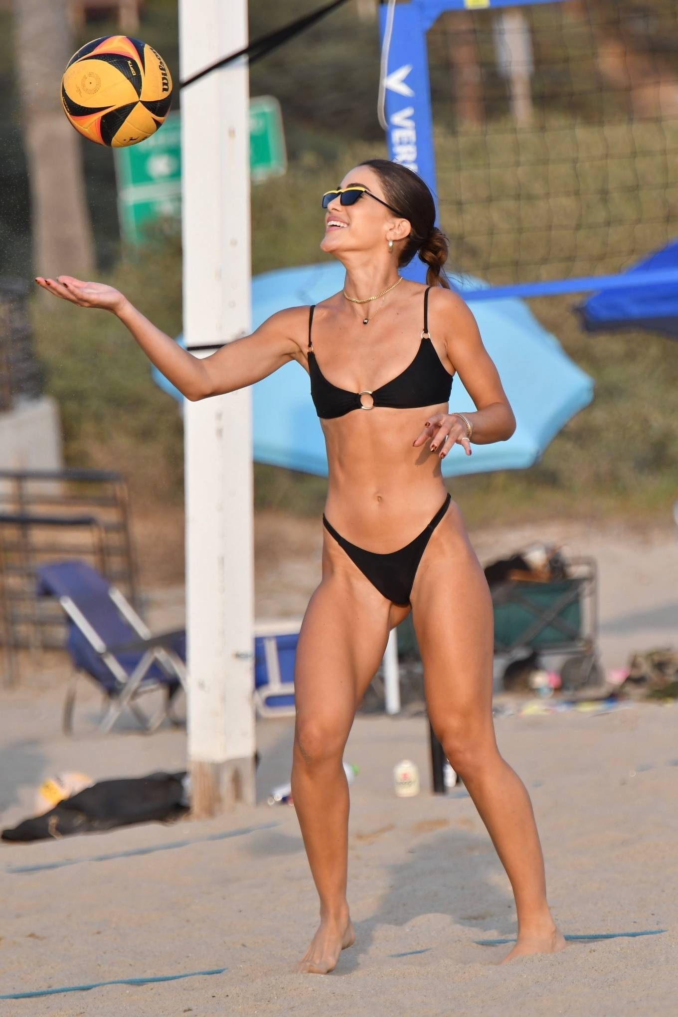 Camila Coelho, black  bikini top, black sunglasses, metal detailing, sexy, thin shoulder strap, scoop neck, plunging, show