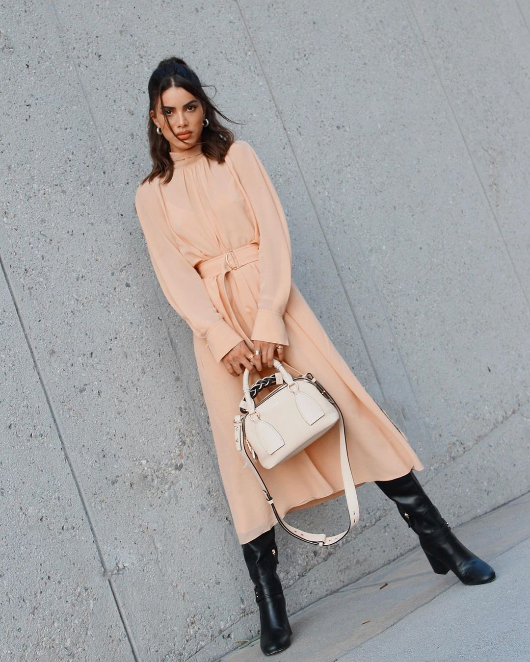 Camila Coelho rocking a flare nude dress with extra long sleeves, a turtleneck, cinched waist and flared hem