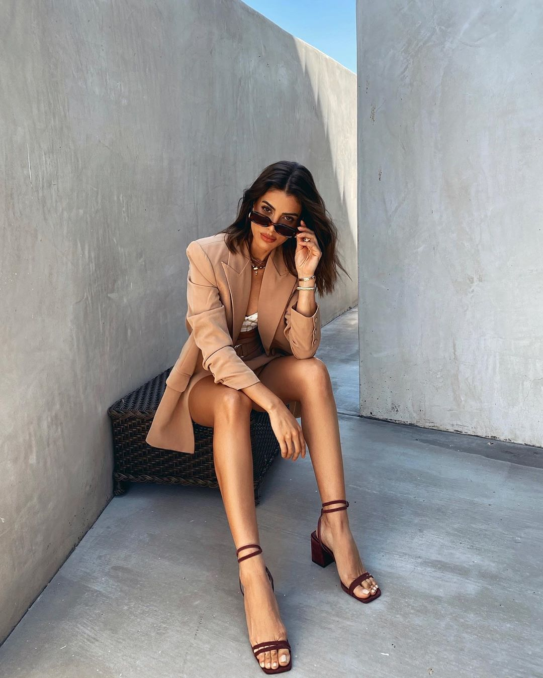 Camila Coelho donning strappy brown open toe sandals with block heel