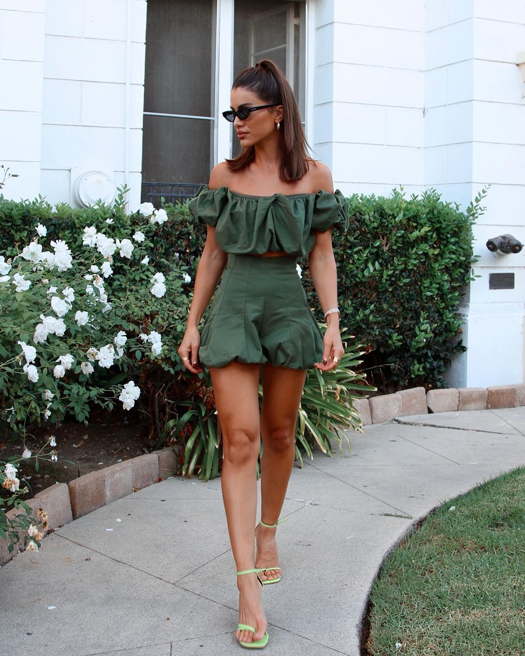 Camila Coelho wearing light green open toe sandals with high heel and thin straps