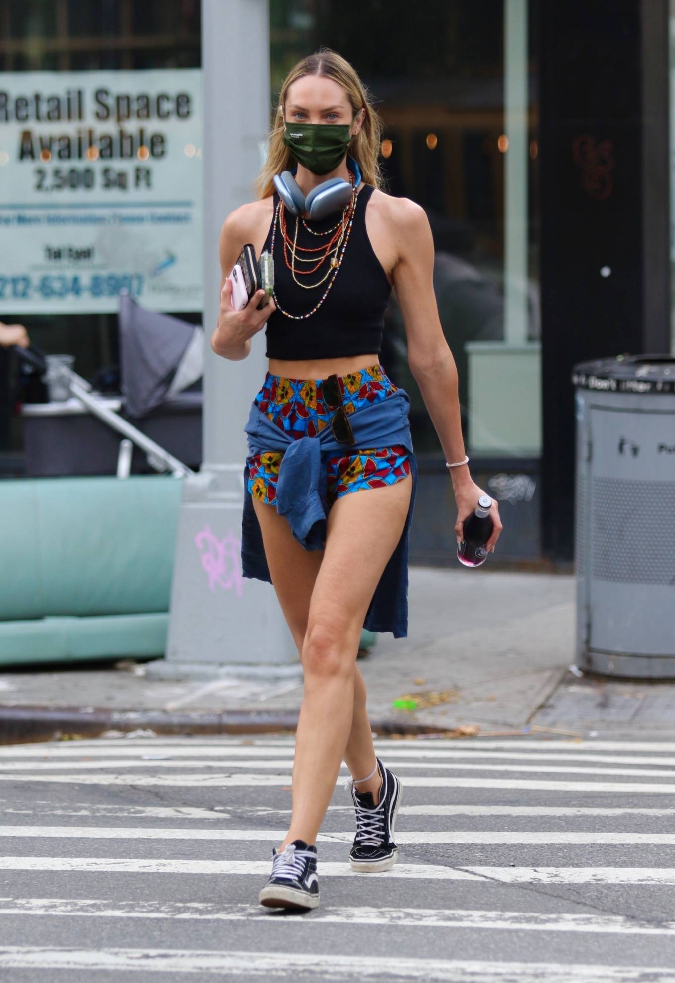 Candice Swanepoel rocking round black Vans lace-up sneakers with flat heel