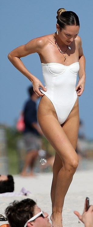 Candice Swanepoel wearing a plunging bodysuit with a nylon material, tie back and cut out