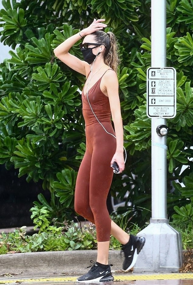 Candice Swanepoel rocking a figure hugging brick red jumpsuit with a nylon material, low back, wrapped detailing in the front in the top portion and spaghetti straps