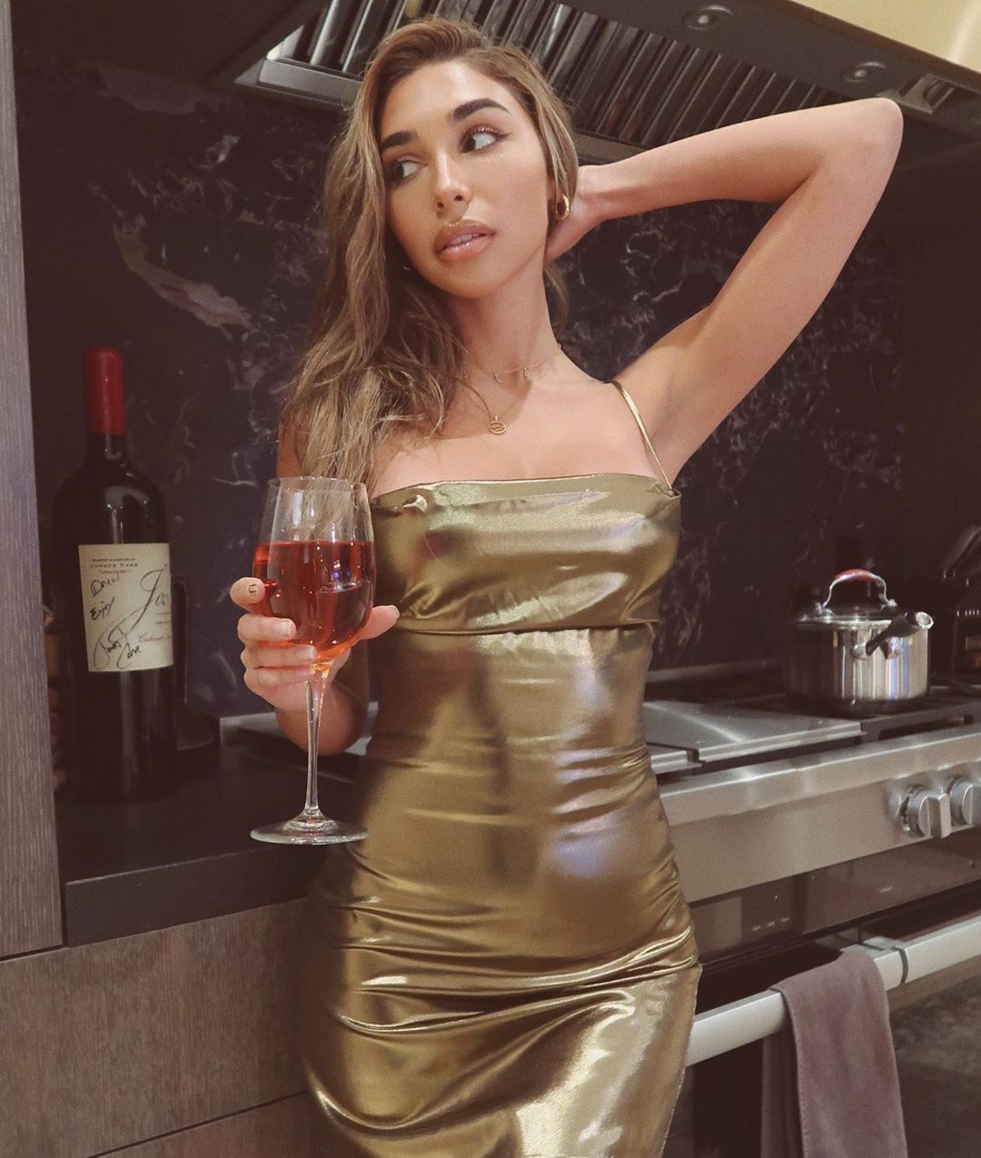 Chantel Jeffries wearing a Plunging shiny metallic gold NBD dress with a satin material, a cowl neck and spaghetti straps
